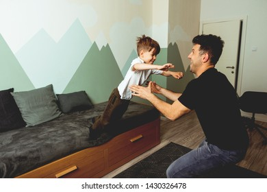 Smiling son playing with his father