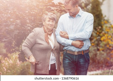 Smiling son relaxing on outdoor with happy mother with walking stick