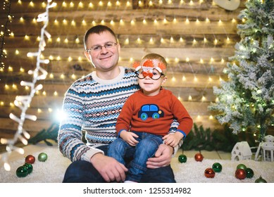 smiling son sitting on father's knee at christmas tree