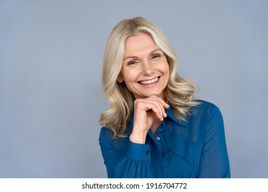Smiling sophisticated 50s middle aged blond business woman looking at camera. Happy mature elegant old lady isolated advertising products or services on grey background. Headshot close up portrait