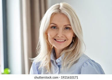 Smiling sophisticated 50s middle aged blond business woman looking at camera. Happy mature elegant old lady professional businesswoman posing at home office. Headshot close up portrait