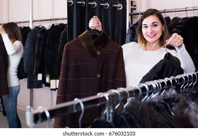 smiling spanish woman choosing sheepskin coat in womens cloths store