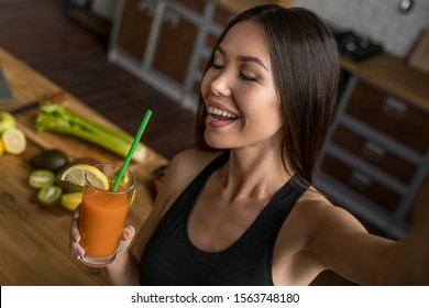 Smiling sport asian woman with smoothie taking selfie in kitchen