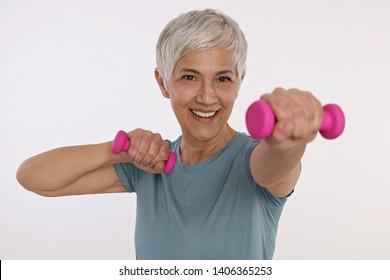 Smiling Sport Mature Woman holding dumbbells isolated on white backround. Active senior lifestyle