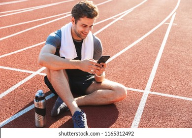 Smiling sportsman finished running at the stadium, resting, using mobile phone