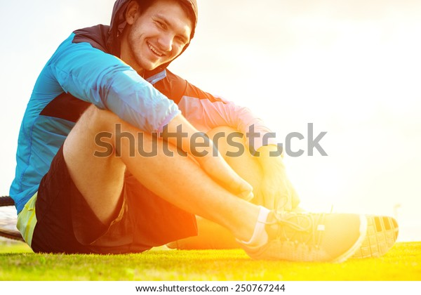 smiling sportsman sitting on the grass in the park