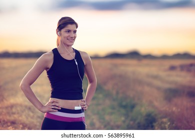 Smiling  Sportswoman listening to music during the workout.
