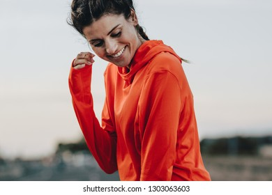 Smiling sportswoman in tracksuit standing outdoors. Fitness woman taking break on after a morning run.