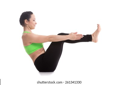 Smiling sporty beautiful girl practices yoga, sitting in boat pose, Navasana, strengthens abdomen, hip flexors, spine, flat belly