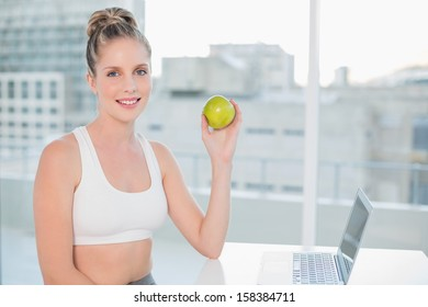 Smiling sporty blonde in bright room holding green apple