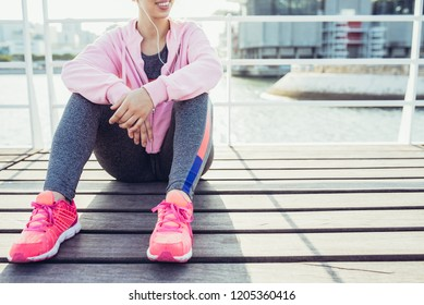 Smiling sporty Caucasian girl in earphones sitting on city quay. Young woman in tracksuit and sneakers relaxing after running by river. Music for training and fitness concept