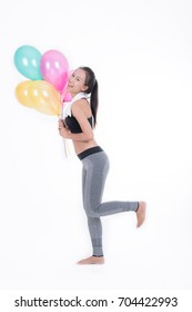 Smiling sporty girl with colorful balloons isolated on white background.Side view.