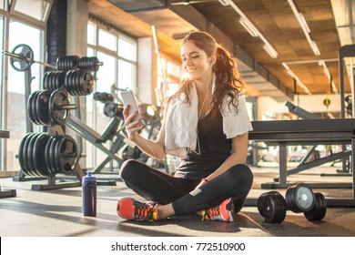 Smiling sporty girl with earphones using phone while sitting down on floor after hard workout in the gym.