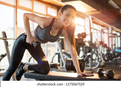 Smiling sporty girl lifting dumbbells on bench in gym