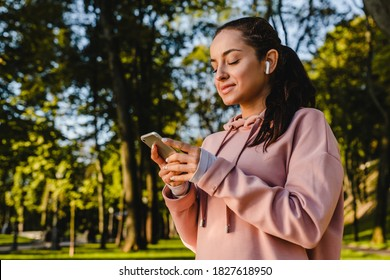 Smiling sporty girl is using her phone with earbuds walking in a park