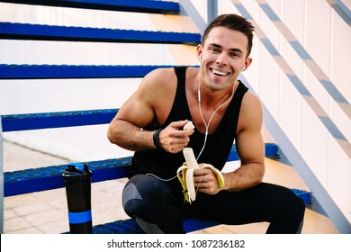 Smiling sporty guy in earphones, eating a banana, after workout, sitting on stairs and looking at camera, outdoors.