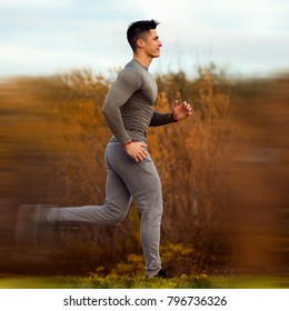 The smiling sporty man is jogging or running at autumn outdoors in nature.