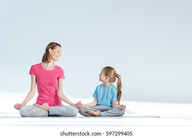 Smiling sporty mother and daughter practicing lotus position with gyan mudra asana isolated on white