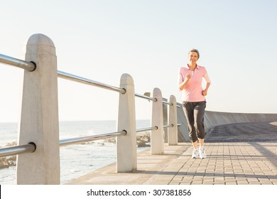 Smiling sporty woman jogging at promenade on a sunny day