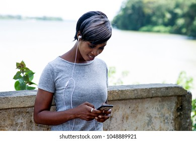 smiling sporty woman leaning against a wall, looking on her phone while listening to music, takes a break in the air after a morning run