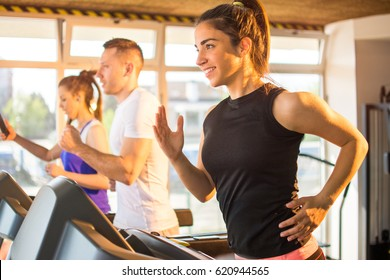 Smiling sporty woman running on a treadmill in gym.