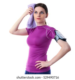 Smiling sporty woman in violet T-short with purple towel, smart phone device and headphones over white isolated background, fitness, sport and lifestyle concept