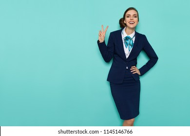 Smiling stewardess in blue formal wear is showing peace hand sign and looking at camera. Three quarter length studio shot on turquoise background.