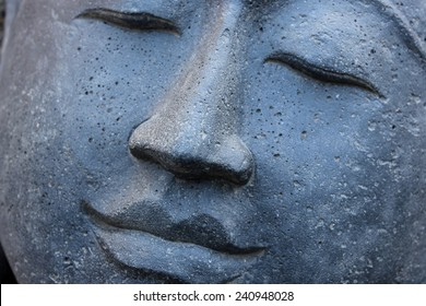 Smiling Stone Buddha Statue face with closed eyes from Indonesia looking to the left