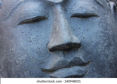 Smiling Stone Buddha Statue face with closed eyes from Indonesia looking to the right