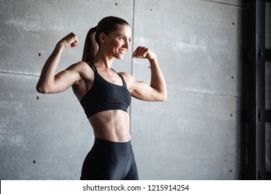 Smiling strong woman in black sportswear. Fitness girl.