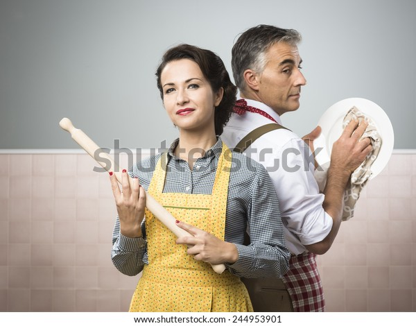Smiling strong woman with rolling pin watching her husband cleaning dishes