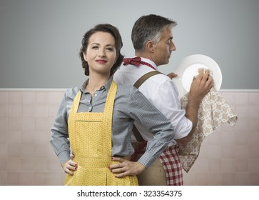 Smiling strong woman watching her husband in apron cleaning dishes
