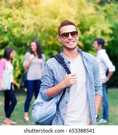 Smiling student in front of a group of friends