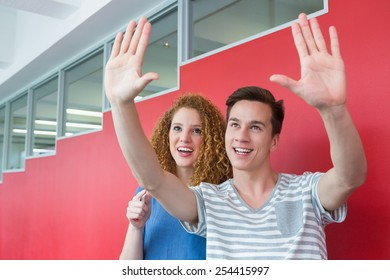 Smiling student gesturing with his friend at the college
