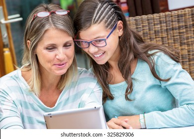 smiling student girl doing homework on tablet with beautiful middle age teacher