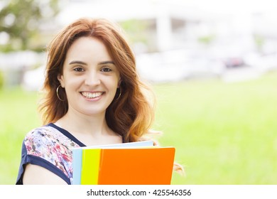 Smiling student girl holding notebooks outdoors at the campus