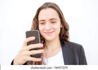 Smiling student girl surfing net on smartphone