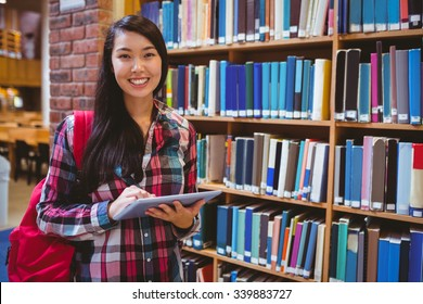Smiling student in library using tablet at the university