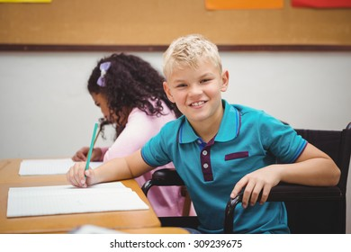 Smiling student sitting in wheelchair at the elementary school