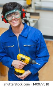 Smiling student standing in a woodwork class and holding a driller
