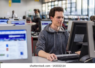 Smiling student using a computer in a library to perform some researches for high school