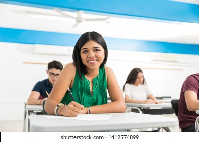 Smiling student writing exam while sitting in classroom at college