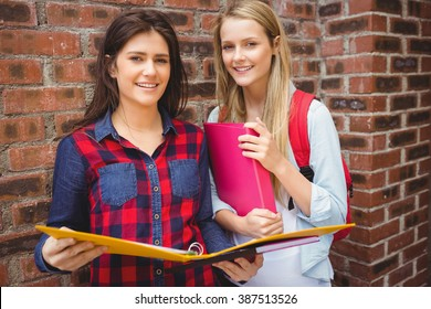 Smiling students with binder looking at camera at university