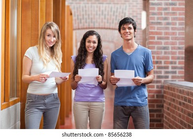 Smiling students holding a piece of paper in a corridor