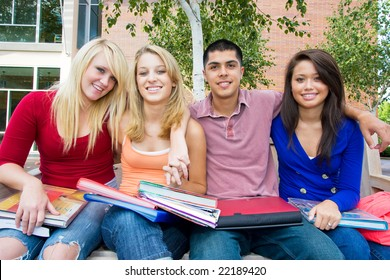 Smiling students sitting on a bench holding books outside of school. There are three girls and one guy, and he has his arms around them. Horizontally framed photo.