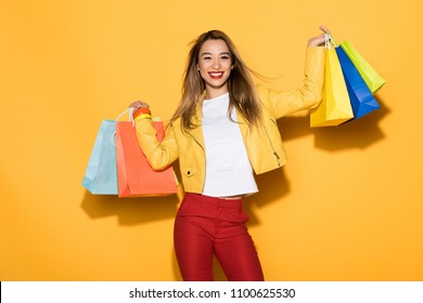 smiling stylish asian woman with shopping bags on yellow background
