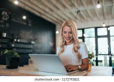 Smiling stylish blonde woman using laptop indoors.