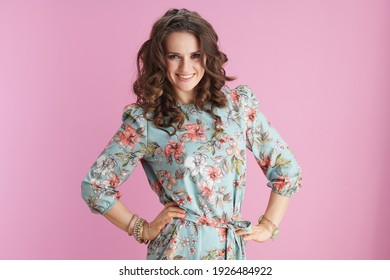 smiling stylish female in floral dress with bracelets isolated on pink background.