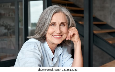 Smiling stylish mature middle aged woman sitting at workplace, portrait. Happy older senior businesswoman, 60s grey-haired lady executive manager looking at camera sitting at office table. Headshot.