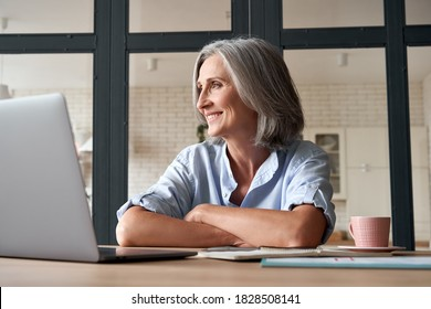 Smiling stylish mature middle aged woman sitting at home office workplace looking away. Happy older senior 60s businesswoman entrepreneur dreaming, relaxing, thinking of business vision concept.